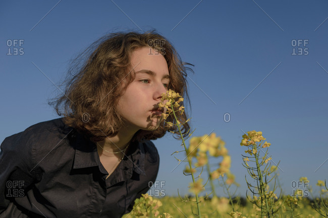 Portrait of teenage girl smelling blossom in rape field