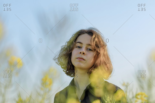 Portrait of teenage girl in rape field against sky