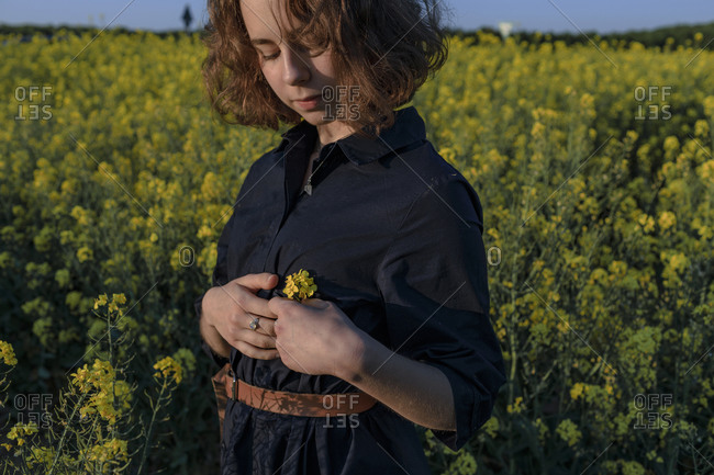 Portrait of teenage girl standing in rape field