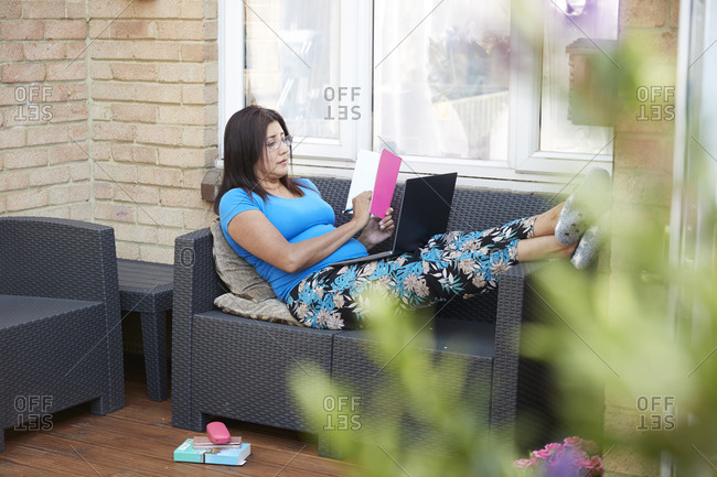 Full length of businesswoman writing in diary while sitting on sofa with laptop at patio