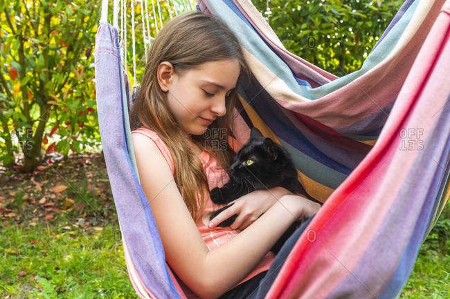 Portrait of girl in hammock cuddling cat