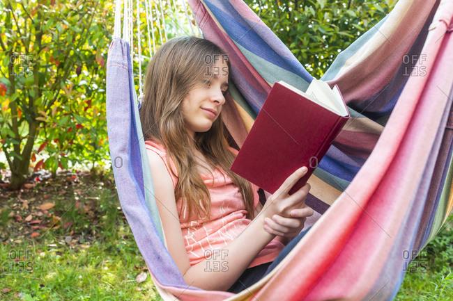 Portrait of girl reading book in hammock