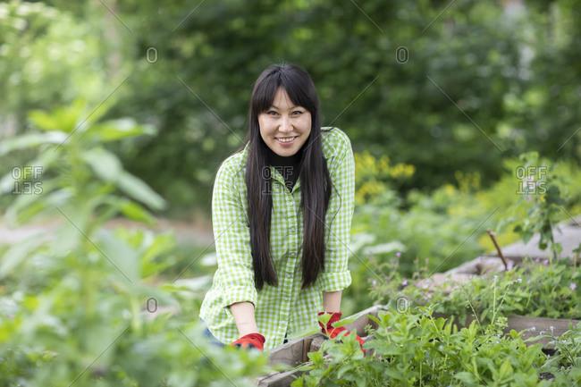 Smiling woman looking at camera in urban garden