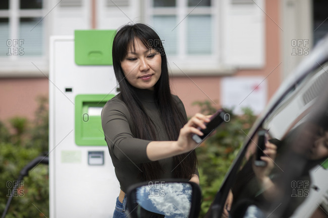 Carsharing- woman renting an electric car using smartphone