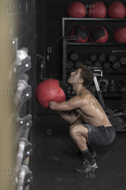 Athlete with an amputated arm exercising with medicine ball at brick wall