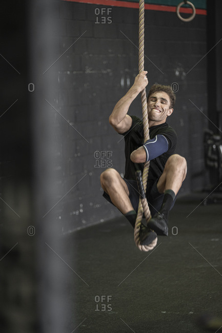 Athlete with an amputated arm climbing rope