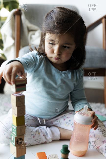 Portrait of toddler girl sitting on the floor playing with wooden building bricks