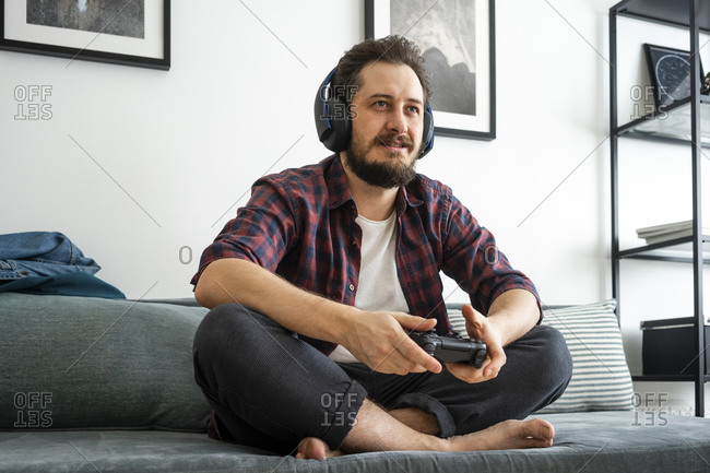 Man sitting on couch and playing video game