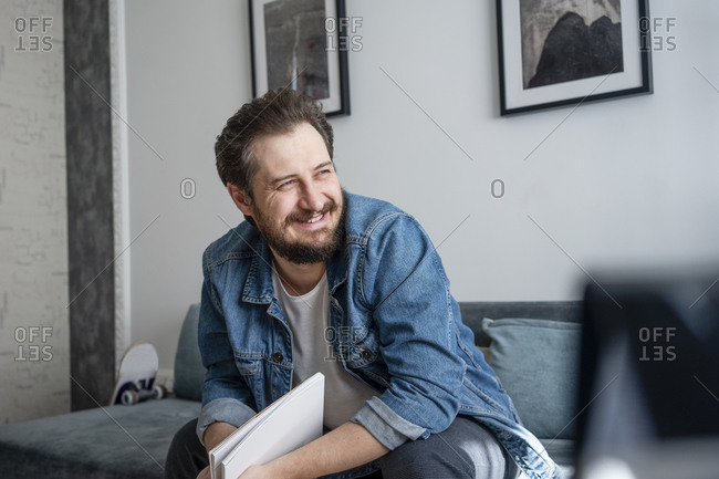 Smiling man with notepad sitting on couch at home