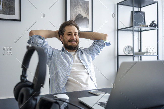 Man using laptop and leaning back at home