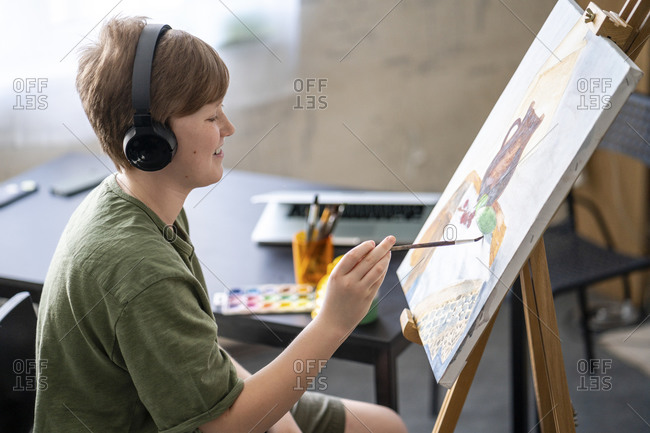 Boy painting at easel and listening to music