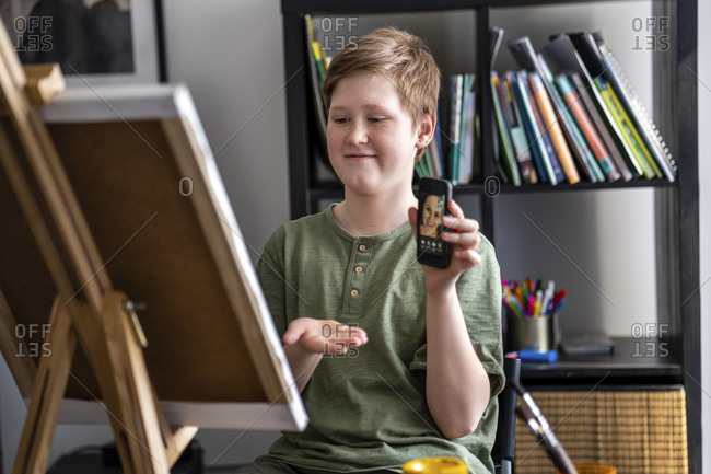 Boy showing via smartphone painting to mother