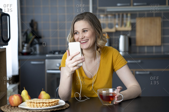 Happy woman with smartphone and earbuds sitting at kitchen table at home