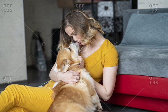 Woman cuddling with her dog in living room at home