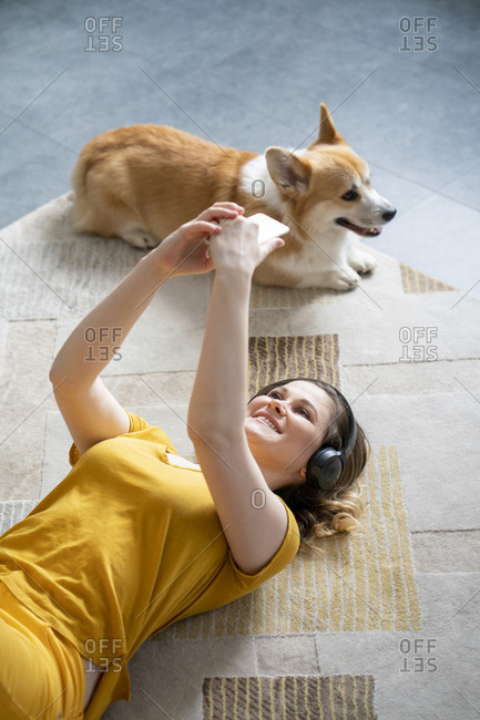 Woman with dog and headphones lying on the floor at home using smartphone