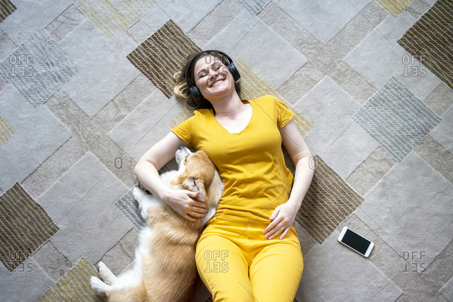 Happy woman with headphones cuddling with her dog in living room at home