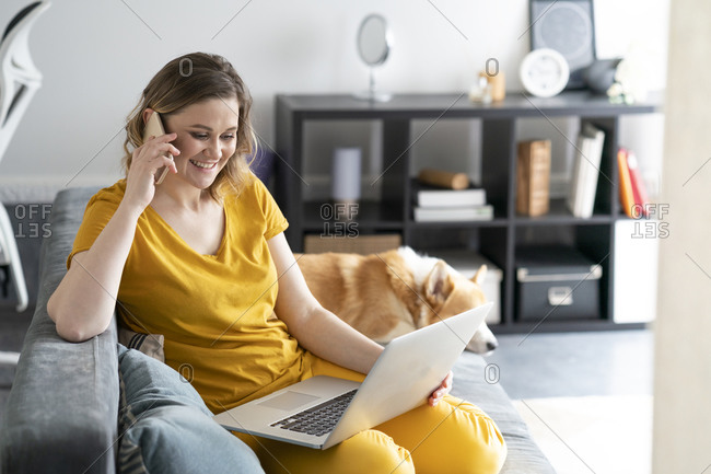 Woman with dog using laptop and cell phone in living room at home