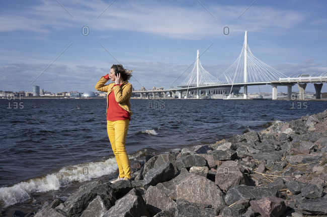 Woman standing at the coast listening to music- Saint Petersburg- Russia