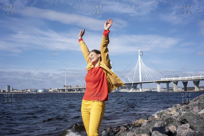 Carefree woman standing at the coast with raised arms- Saint Petersburg- Russia
