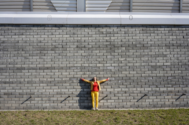 Woman standing at a brick wall listening to music with headphones