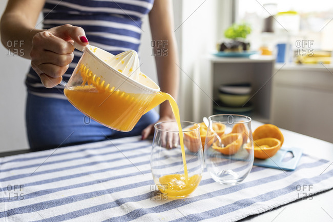 Woman pouring freshly squeezed orange juice into glasses