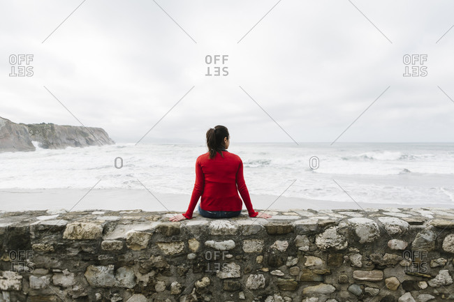 Rear view of relaxed female tourist sitting on retaining wall while looking at sea against sky- Itzurun- Zumaia- Spanish Basque Country- Spain