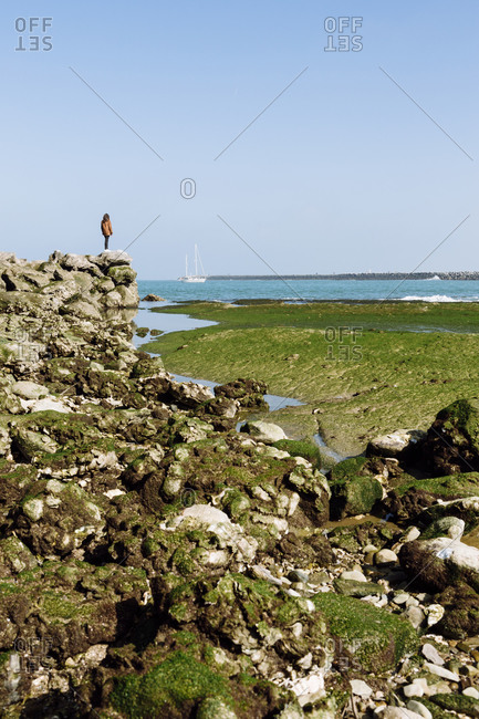 Woman standing at the edge of rock formation at beach against clear blue sky during sunny day