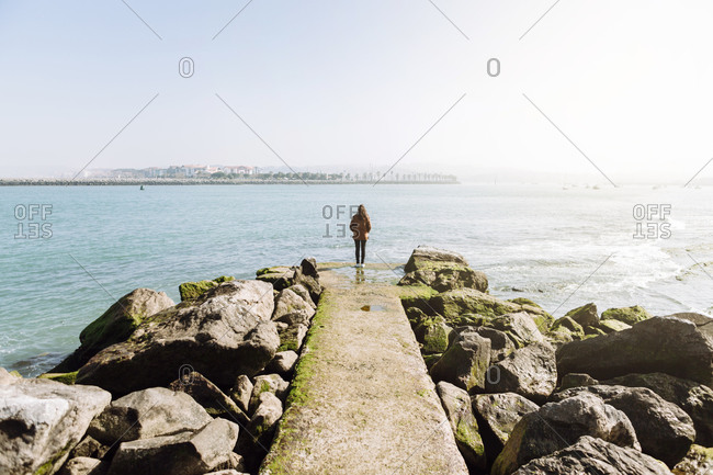 Full length rear view of woman standing on pier while looking at sea against clear sky during sunny day