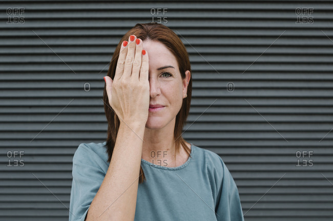 Woman covering one eye with her hand