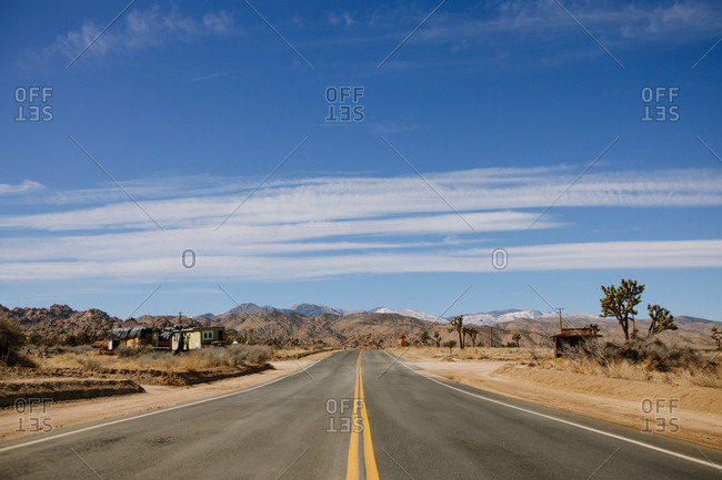 Straight asphalt road going through sandy terrain with dry grass and mountains on background of cloudy sky on heat day in California