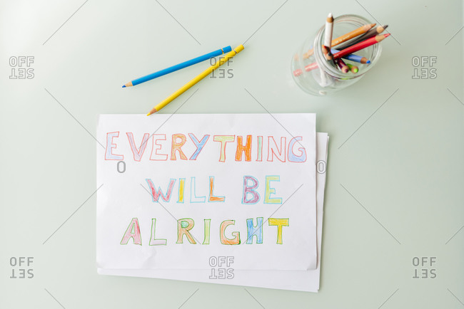 Top view of composition with multicolored pencils in glass jar and colorful drawing on paper with positive inscription placed on white table
