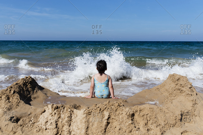 Back view of unrecognizable little girl in swimsuit sitting on sandy beach against sea waves and enjoying summer holidays in sunny day