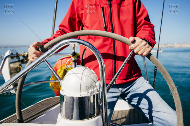 Crop unrecognizable man in red jacket and jeans standing at steering wheel while sailing in sea on modern vessel