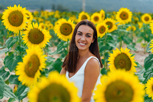 Happy adult woman smiling and looking at camera while sitting amidst bright fresh sunflowers in countryside field