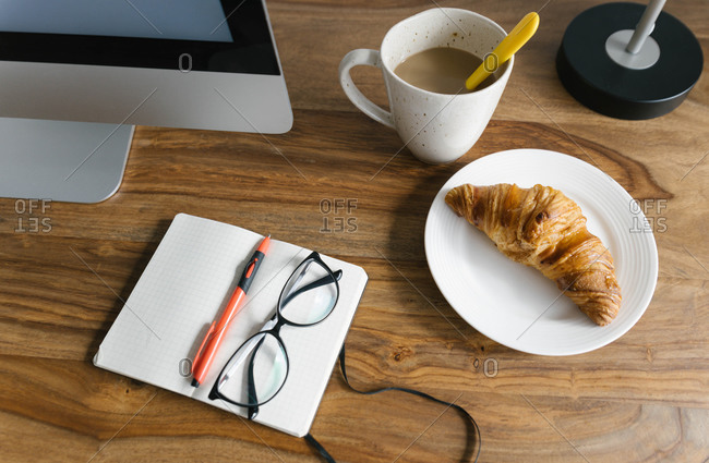 From above of white cup of hot aromatic coffee with yellow spoon arranged with opened planner and crispy fresh croissant on wooden table on daytime