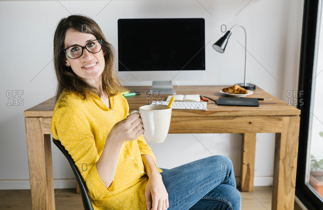 Happy female freelancer in casual outfit and eyeglasses sitting on chair with cup of hot beverage and legs crossed while looking at camera during coffee break at home