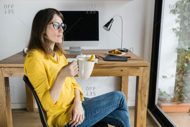 Pensive female freelancer in casual outfit and eyeglasses sitting on chair with cup of hot beverage and legs crossed while looking out of window during coffee break at home