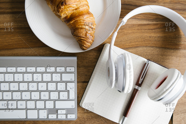 Top view of crispy fresh croissant arranged with opened planner and headphones on workplace wooden table on daytime