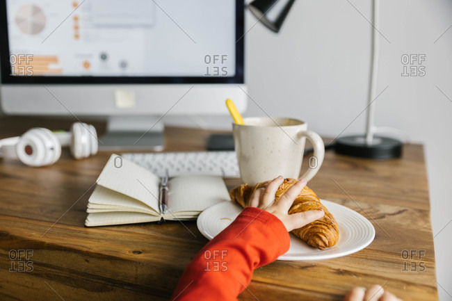 Unrecognizable cute child in orange wear getting tasty croissant from tall desktop with computer cup of coffee and headphones at home