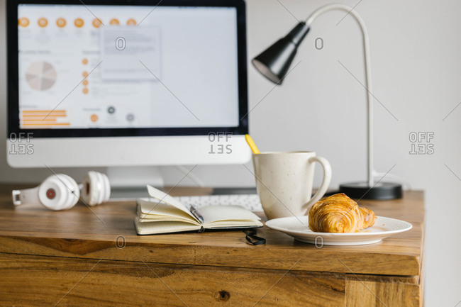 Interior of modern workspace with a breakfast, diary and headphones on wooden desktop above desk locating near window in light trendy living room at home