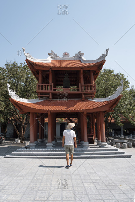 Back view of male tourist wearing casual clothes and conical hat sightseeing during vacation and walking towards pagoda