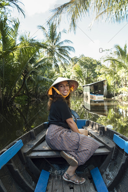 Smiling female tourist in summer outfit and conical hat sitting in wooden boat and floating along river surrounded by tropical trees in Can Tho