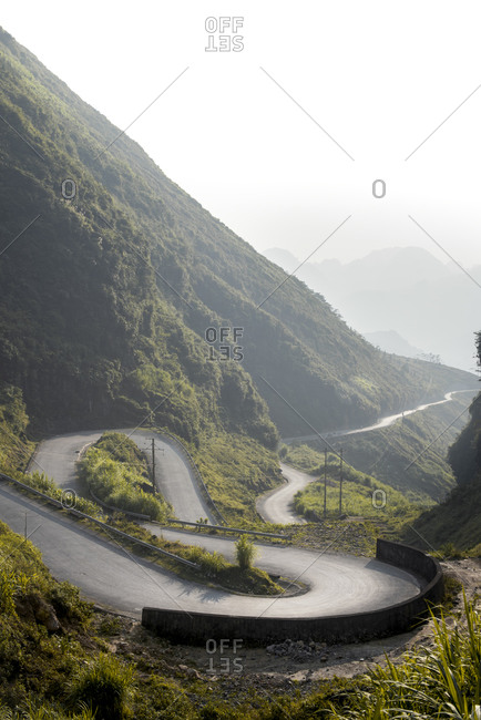 Spectacular landscape of winding paved route in green tropical highlands during foggy morning in summer
