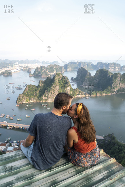 From above back view of loving couple sitting on metal roof and observing picturesque view of Halong bay in Vietnam while they kiss