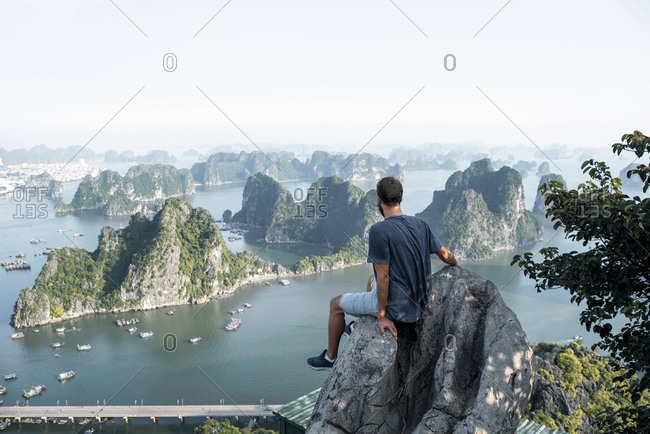 High angle back view of male traveler in casual clothes sitting on rock and enjoying amazing scenery of Halong bay with rocky sticking cliffs during vacation