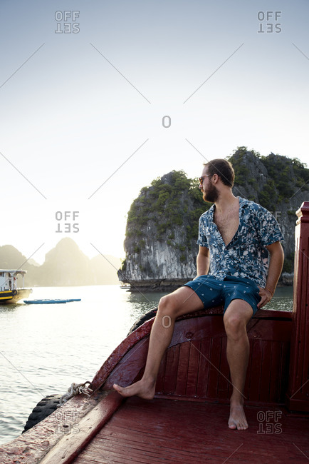 Side view of traveling male in casual wear resting on wooden quay and admiring amazing scenery of tranquil water and mountains