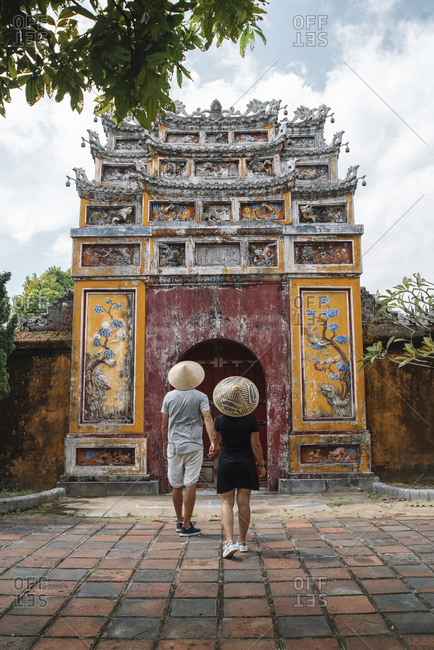 Back view of couple holding hands and walking towards shabby arch of Buddhist temple while sightseeing during vacation in Vietnam