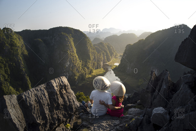 From above back view of couple of tourists in conical hats hugging while sitting on high rocky top of Mua cave and admiring magnificent tropical valley in ridges