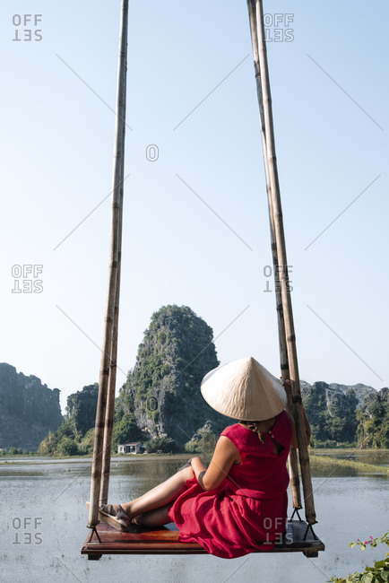 Back view of unrecognizable female tourist in casual clothes and conical hat sitting on wooden swing and admiring amazing scenery of rocks in water