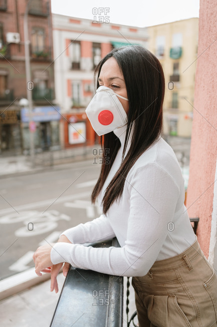 Side view of young female in casual outfit and protective mask standing on balcony in city and looking away while spending day in self isolation at home during coronavirus pandemic